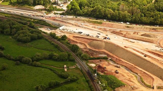 Devon County Council. The Aller Tunnel, is a 21m span, 270m long structure carrying the highly skewed new A380 dual-carriageway over the Torquay branch line. It comprises U shaped, pre-cast beams placed on high level bank-seats, in turn supported by reinforced earth abutment walls. The foundations required extensive ground improvement works achieved with an innovative soil improvement techniques using cement bound site won fill