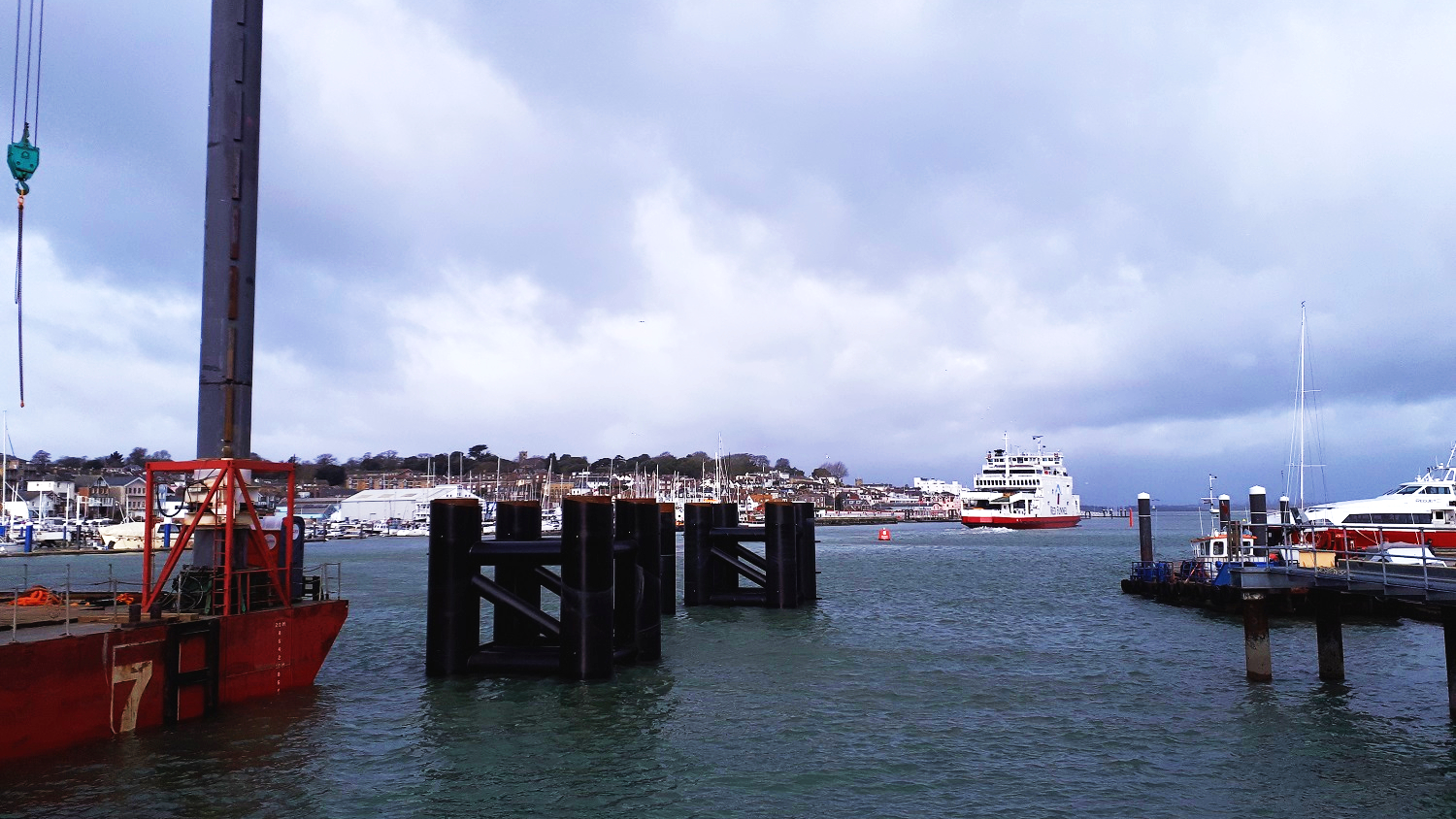 The lay-by berth nears completion with all piles and jacket structures installed. In the distance a Red Funnel passenger ferry leaves East Cowes for Southampton. March 2019 © Ramboll