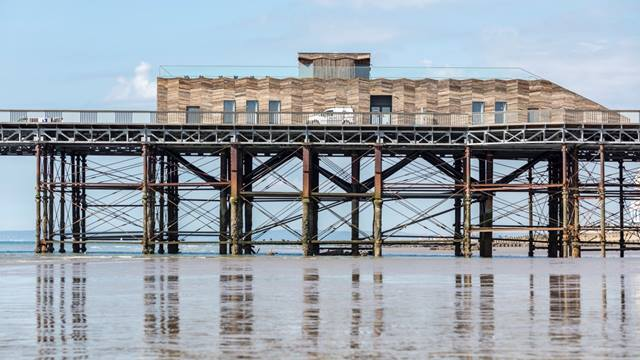 Daniel Shearing. The new visitor centre on Hastings Pier is a modern Cross Laminated Timber building which does not attempt to be a pastiche of 19th century style. The lightweight carbon negative structure features wall-cladding made with timber salvaged from the old pier deck.
