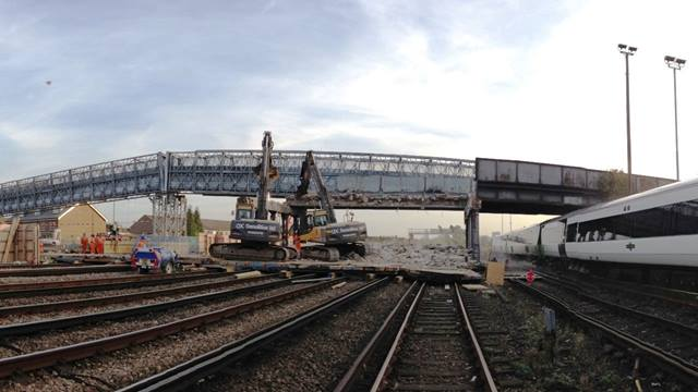 GRAHAM Construction. Demolition involved removing the structure span by span in a series of rail track possessions over a two month period. The temporary footbridge can be seen in the background.